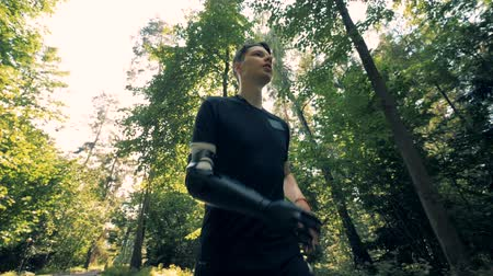 handikap : A man with an artificial arm is running along the alley. Futuristic human cyborg concept. Stok Video