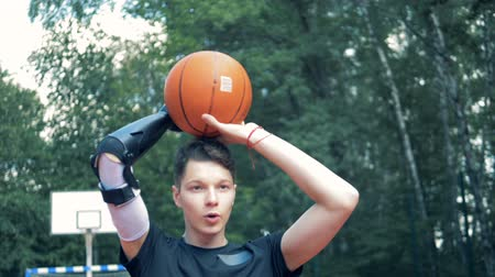 challenged : Teenage boy with a prosthetic hand is throwing a basket-ball.