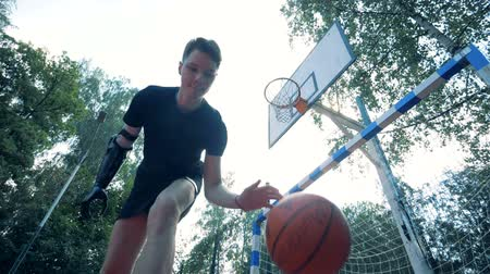 physically : Slow motion juggling of a basket-ball performed by a young man with a futuristic prosthetic arm Stock Footage