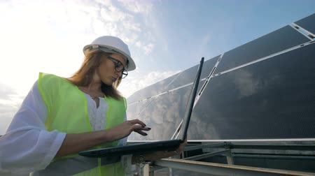 energetyka : Attractive woman is operating her laptop while being near a solar construction