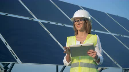energetyka : Outdoors solar battery with a female engineer standing beside it and smiling Wideo
