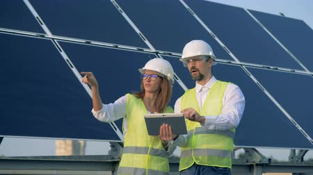 energetyka : Construction employees in the process of discussion and planning while standing beside a solar panel Wideo