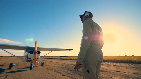 pilots : One man comes to a biplane, examining its propeller and wings. 4K. Stock Footage