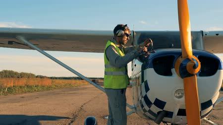 hélice : One person checks a gas level on a small plane. Technical condition concept.