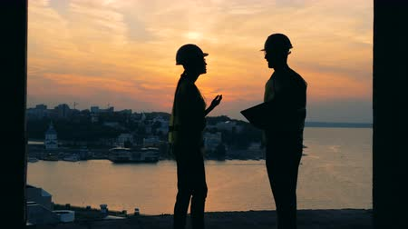 geodesy : Two builders working on a sunset background, side view. Stock Footage