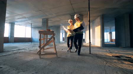 mimar : Architects walking inside a building, close up. Stok Video