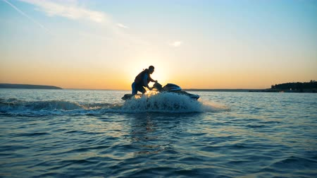 motorbot : Young person riding a waverunner on a sunset background, side view. Stok Video