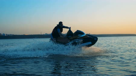 mobilet : Man in a life jacket on a jet ski, close up.
