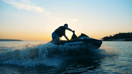 jet ski : Person drives on a waverunner on a sunset background, side view.