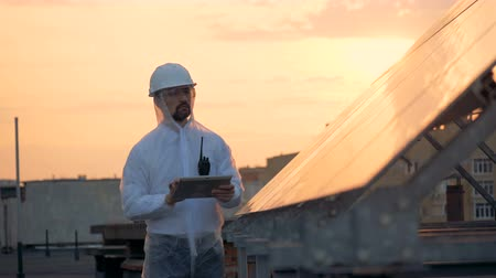 modul : Solar installation and a male specialist working near it at the sunset Stock mozgókép