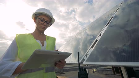 inspector : Female solar inspector is working on her computer while standing on the rooftops Stock Footage