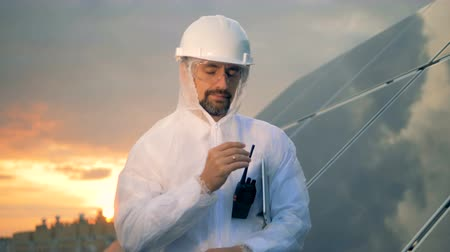 energetyka : Smiling solar engineer is adjusting his glasses and looking straight into the camera