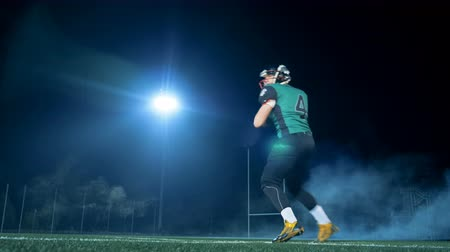 power equipment : A sportsman playing American football. Man stands in a pose in the stadium, then throws a ball. Stock Footage