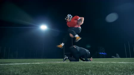 savunma oyuncusu : American football player jumps over another player, while competing on an empty field.