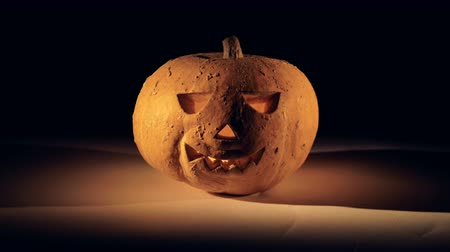 perverso : Zooming-in footage of a halloween pumpkin with a candle in it