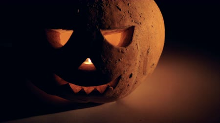 grão : Decorative jack-o-lantern with a glowing candle inside of it Stock Footage