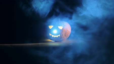 wicked : Radiating jack-o-lantern is standing in the clouds of smoke Stock Footage