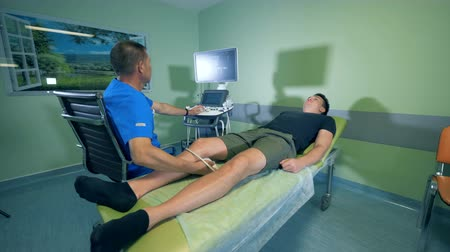 sonography : Man lies on a bed while a doctor scans his knee with a ultrasound device.