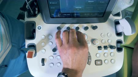 sonography : Male doctor pushes buttons on a ultrasound device, top view.