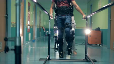 tentar : Recovery therapy at a clinic. Patient tries to move legs, wearing special prosthesis. Stock Footage