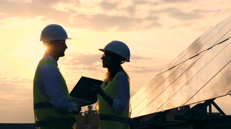 hardhat : Workers talking on a sunset background, side view.