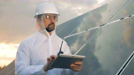 fotovoltaica : A man in uniform works with a tablet, close up.