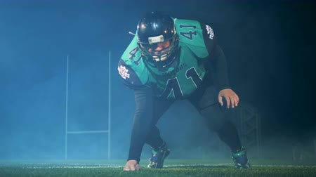 agrese : American football player stands in a special pose ready to play American football on a stadium. Dostupné videozáznamy