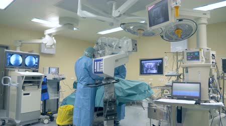 csapatmunka : Innovative medicine concept. One surgeon uses modern microscope and surgical robot during a surgery at a clinic.