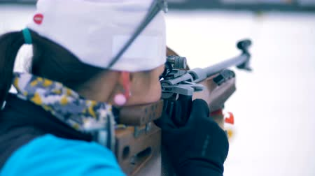 biathlon : Woman holds a biathlon rifle while aiming at a target. 4K.