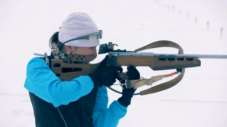 biathlon : Skier stands with a rifle, side view. Stock Footage