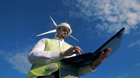 industry : An engineer stands on a wind turbine background. Alternative energy concept.