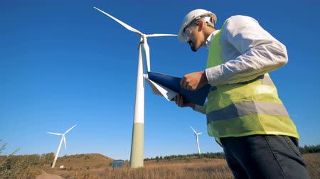 tvořit : A person holds a clipboard while walking near wind turbines. Renewable electririty, green energy concept. Dostupné videozáznamy