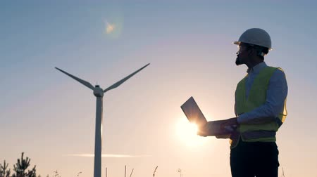 tvořit : Male engineer holds a laptop, types on it and checks electric windmills. Renewable electririty, green energy concept.