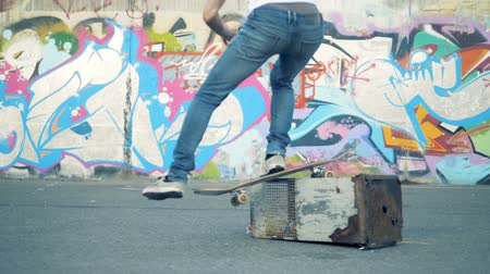 kickflip : Skateboarder fail. Skaterboarder jumps over a bucket, slow motion.
