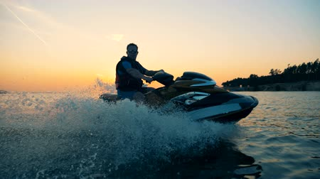 jet ski : Driver of a water scooter is looking into the camera while riding Stock Footage