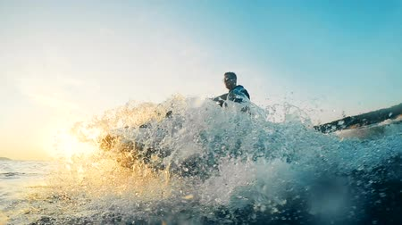 equipped : Male jetskier is sailing along the lake on his waverunner Stock Footage