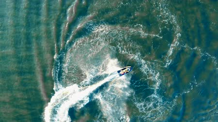 pwc : Splashes and waves formed after a water scooter sailing across the sea in a view from above