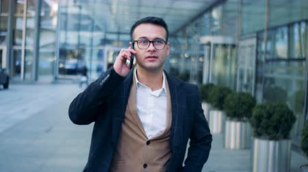 motivados : Telephone conversation of a businessman walking in the urban street, downtown. Red epic cinema camera footage.