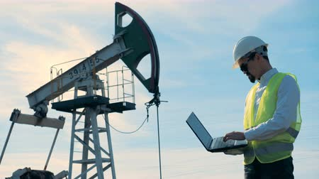 fosilní : A person with a laptop works on an oilfield near oil pumps.