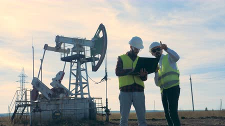 diesel fuel : Two workers standing on an oilfield near oil pumps. Stock Footage