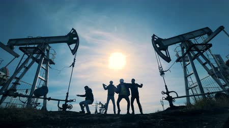 petroleum refinery : Four engineers dancing, having fun near oil towers. Stock Footage
