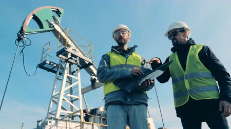 kask : Workers talk on an oil derrick background. Fossil Fuel, Oil industry concept. Stok Video