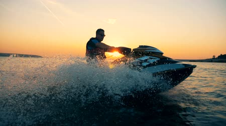 jet ski : A man is riding a jet-ski along the coastline during sunset