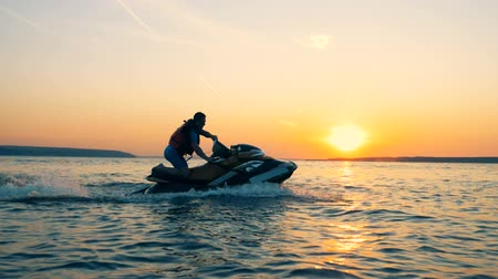 jet ski : A man is running ajet ski across sunset waterscape