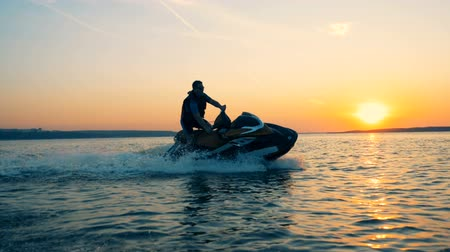 моторная лодка : Sunset lake with a man driving along it on his waterbike, jet ski.