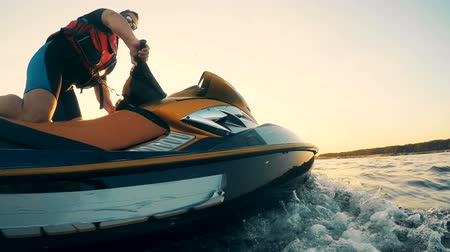 pwc : Sunset waterscape with a professional riding a waterbike, waverunner