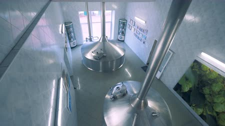 two rows : Two containers in brewery. Steel fermentation vessels.