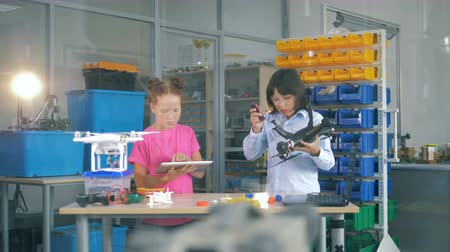 propeller toy : Children working in a laboratory room with UAV, drones, copters. Stock Footage