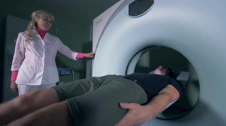 radiologia : Female medical worker is controlling process of patients moving out of an MRI machine
