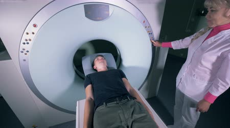 screening : Patient is entering an MRI mechanism under female doctors supervision